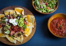 Selbst gemachte Nachos mit Tortilla-Chips Käse und Guacamole Stockfotos