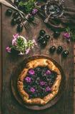 Selbst gemachte offene Kirschetorte oder galette auf hölzernem rustikalem Küchentischhintergrund mit Stau, Blumen und Tischbestec Stockbild