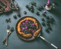 Selbst gemachte offene Kirschtorte auf hölzerner Platte und rustikaler Küchentischhintergrund mit Stau und Tischbesteck, Draufsic Lizenzfreie Stockfotos
