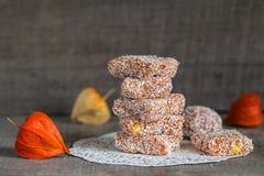 Selbst gemachte orange Fruchtsüßigkeit in den Kokosnussflocken Stockfotografie