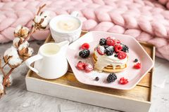 Selbst gemachte Pfannkuchen-Cappuccino-riesige Merinowolle-Decken-rosa Platten-Sahne-Beeren-Kaffee-gesundes Pastellfrühstück stockbilder