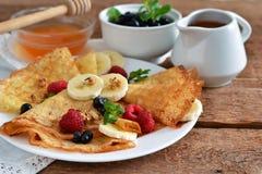 Selbst gemachte Pfannkuchen mit Banane, Beeren und Honig Lizenzfreie Stockfotos