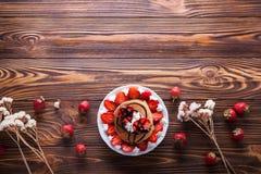 Selbst gemachte Pfannkuchen mit dem Erdbeer-, Schlagsahne- und Schokoladenbelag, verziert mit Blumen auf hölzernem Hintergrund Stockfotografie