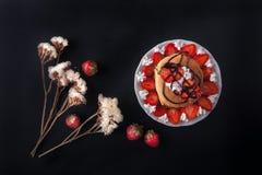 Selbst gemachte Pfannkuchen mit dem Erdbeer-, Schlagsahne- und Schokoladenbelag, verziert mit Blumen auf schwarzem Hintergrund Stockfotografie