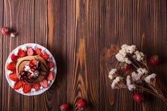 Selbst gemachte Pfannkuchen mit dem Erdbeer-, Schlagsahne- und Schokoladenbelag, verziert mit Blumen auf schwarzem Hintergrund Lizenzfreie Stockfotografie