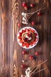 Selbst gemachte Pfannkuchen mit dem Erdbeer-, Schlagsahne- und Schokoladenbelag, verziert mit Blumen auf schwarzem Hintergrund Lizenzfreies Stockfoto