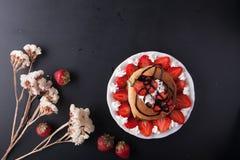 Selbst gemachte Pfannkuchen mit dem Erdbeer-, Schlagsahne- und Schokoladenbelag, verziert mit Blumen auf schwarzem Hintergrund Lizenzfreie Stockfotos