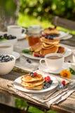 Selbst gemachte Pfannkuchen mit frischen Blaubeeren und Honig lizenzfreies stockfoto