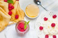 Selbst gemachte Pfannkuchen mit Honig, Himbeeren, Hüttenkäse mit Pulverzucker Flache Lage, Draufsicht Kopieren Sie Platz Eco Art Stockfotografie