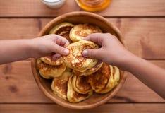 Selbst gemachte Pfannkuchen mit Honig und Glas Milch im hölzernen Teller Stockfoto