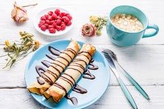 Selbst gemachte Pfannkuchen oder russischer Blini mit Schokoladensoße auf Platte auf weißem hölzernem Hintergrund Stockbild