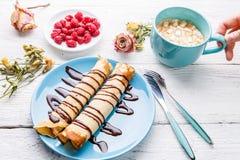 Selbst gemachte Pfannkuchen oder russischer Blini mit Schokoladensoße auf Platte auf weißem hölzernem Hintergrund Stockfotografie