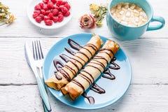 Selbst gemachte Pfannkuchen oder russischer Blini mit Schokoladensoße auf Platte auf weißem hölzernem Hintergrund Lizenzfreie Stockfotografie