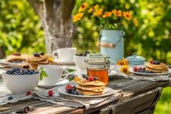 Selbst gemachte Pfannkuchen zum Frühstück im sonnigen Garten lizenzfreies stockbild