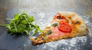 Selbst gemachte Pizza auf Schiefer mit Salat lizenzfreie stockbilder