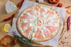 Selbst gemachte Pizza mit Meeresfrüchten und roten Fischen auf einem hölzernen Hintergrund mit Obst und Gemüse mit Gewürzen stockfoto