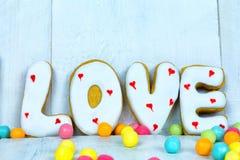 Selbst gemachte Plätzchen in Form von einem Herzen oder ich liebe dich Wörtern als Geschenk zu einem geliebten an Valentinsgruß ` Stockfotos