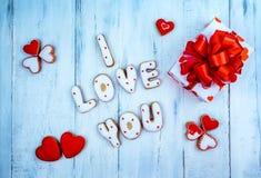 Selbst gemachte Plätzchen in Form von einem Herzen oder ich liebe dich Wörtern als Geschenk zu einem geliebten an Valentinsgruß ` Lizenzfreies Stockfoto