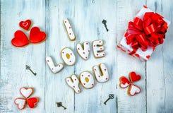 Selbst gemachte Plätzchen in Form von einem Herzen oder ich liebe dich Wörtern als Geschenk zu einem geliebten an Valentinsgruß ` Stockbild