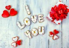 Selbst gemachte Plätzchen in Form von einem Herzen oder ich liebe dich Wörtern als Geschenk zu einem geliebten an Valentinsgruß ` Lizenzfreies Stockbild