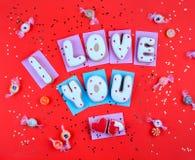 Selbst gemachte Plätzchen in Form von einem Herzen oder ich liebe dich Wörtern an Valentinsgruß ` s Tag auf Draufsicht des roten  Stockfotos