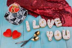 Selbst gemachte Plätzchen in Form von einem Herzen oder ich liebe dich Wörtern an Valentinsgruß ` s Tag auf einer Draufsicht des  Lizenzfreie Stockfotografie