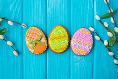 Selbst gemachte Plätzchen mit Zuckerglasur in Form eines Eies für Ostern Köstliche Ostern-Plätzchen auf einem blauen Hintergrund  Lizenzfreies Stockbild