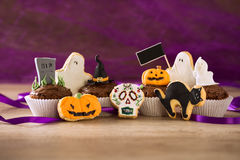 Selbst gemachte Plätzchen und kleine Kuchen Halloweens auf purpurrotem Spinne backgro Lizenzfreies Stockbild
