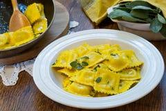 Selbst gemachte Ravioliteigwaren mit weiser Buttersoße, italienische Nahrung Lizenzfreie Stockbilder