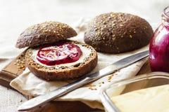Selbst gemachte Roggenbrötchen mit Leinsamen, indischem Sesam und weißem Mohn dienten mit Butter und Stau stockfoto