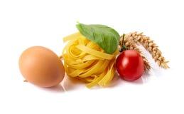 Selbst gemachte rohe Eiernudeln mit der Tomate und Basilikum lokalisiert auf Weiß lizenzfreie stockbilder
