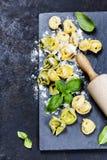 Selbst gemachte rohe italienische Tortellini- und Basilikumblätter Lizenzfreie Stockfotografie