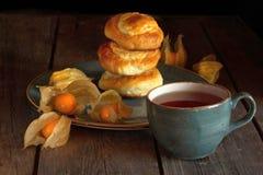 Selbst gemachte Rollen mit Hüttenkäse und Physalis und eine Tasse Tee auf einem Holztisch stockfotografie