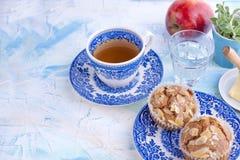 Selbst gemachte süße Muffins mit Mandeln für Frühstück Tee und ein Glas Wasser in den Weinleseblautellern Frucht und Öl Freier Ra Stockfotografie