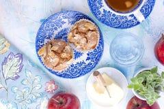Selbst gemachte süße Muffins mit Mandeln für Frühstück Tee und ein Glas Wasser in den Weinleseblautellern Frucht und Öl Freier Ra Stockbild