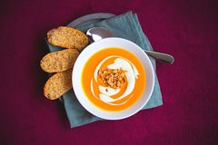 Selbst gemachte Süßkartoffel- und Karottensuppe mit den Paprikas und Ingwer verziert durch Sauerrahm und gebratene Erdnuss in der Lizenzfreie Stockfotografie
