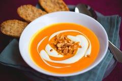 Selbst gemachte Süßkartoffel- und Karottensuppe mit den Paprikas und Ingwer verziert durch Sauerrahm und gebratene Erdnuss in der Lizenzfreies Stockfoto