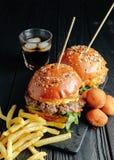 Selbst gemachte saftige Burger auf hölzernem Brett, Käsebälle mit Pommes-Frites und Glas Kolabaum Beschneidungspfad eingeschlosse lizenzfreie stockfotos