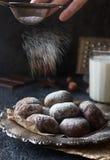 Selbst gemachte Schokolade krümmt sich im Puderzucker, in den Schokoladenplätzchen mit Sprüngen und in einem Glas Milch Lizenzfreies Stockfoto