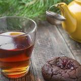 Selbst gemachte Schokoladenplätzchen mit einer Glasschale schwarzem Tee stockfotografie
