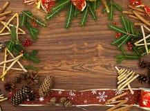 Selbst gemachte Spielwaren und Tannenbaumaste auf hölzernem braunem Hintergrund Lizenzfreies Stockfoto