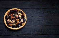 Selbst gemachte Torte mit Pflaumen und Äpfeln auf dunklem hölzernem Hintergrund Stockfotos