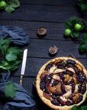 Selbst gemachte Torte mit Pflaumen und Äpfeln auf dunklem hölzernem Hintergrund Stockfoto