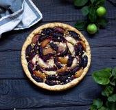 Selbst gemachte Torte mit Pflaumen und Äpfeln auf dunklem hölzernem Hintergrund Lizenzfreie Stockfotografie