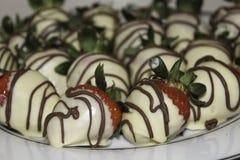Selbst gemachte weiße Schokolade bedeckte Erdbeeren mit Milchschokoladenieselregen stockbild
