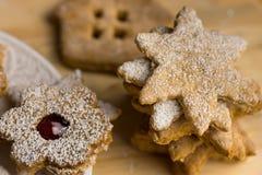 Selbst gemachte Weihnachtenlebkuchen- und linzerplätzchen mit dem Stau oben pulverisiert, auf einem hölzernen Brett, Abschluss Stockfotos