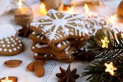 Selbst gemachte Weihnachtslebkuchenplätzchen mit Dekorationen und Ñ- hristmas Lichtern Stockbilder