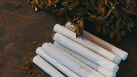 Selbst gemachte Zigaretten oder Rolle-oben des Filters nahe bei den trockenen Tabakblättern angefüllt mit gehacktem Tabak stock video footage