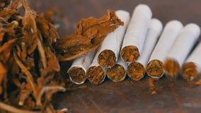 Selbst gemachte Zigaretten oder RolleUPS sind auf dem Tisch nahe bei großen Blättern des trockenen Tabaks stock video