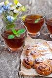 Selbst gemachte Zimtbrötchen mit Teeschalen und Bündel wilden Blumen Stockfotografie